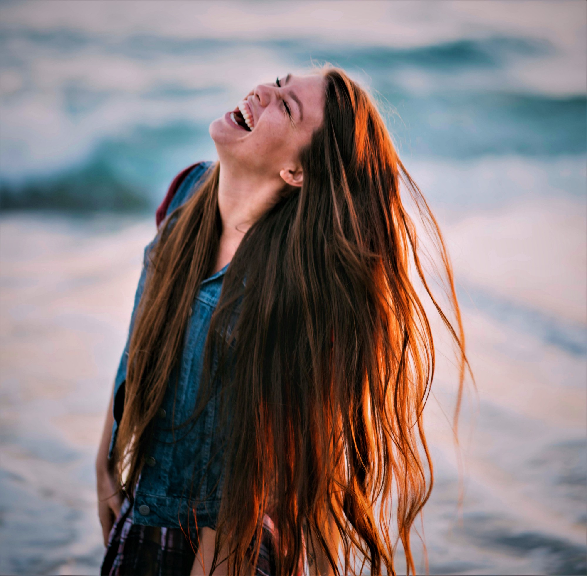 happy girl with long red hair standing in ocean waves looking up to the sky and laughing