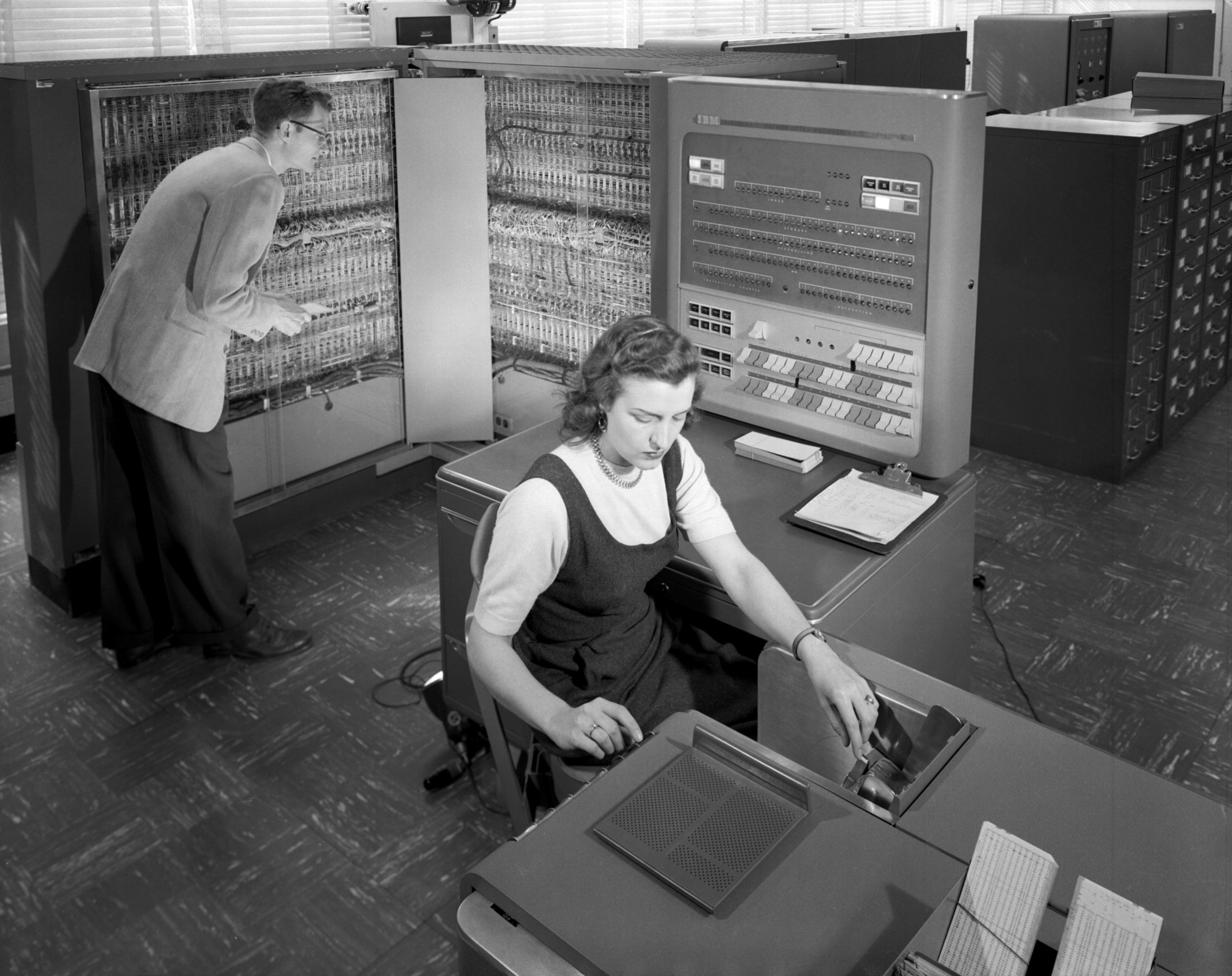 Man and woman working with IBM type 704 electronic data processing machine.