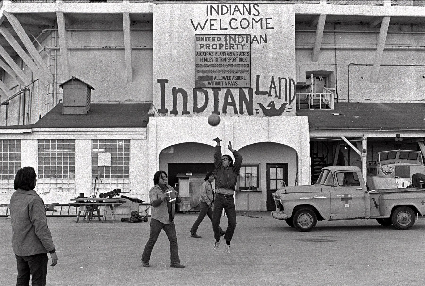 Native Americans play basketball at Alcatraz, in front of a sign that reads Indians Welcome, Indian Land.