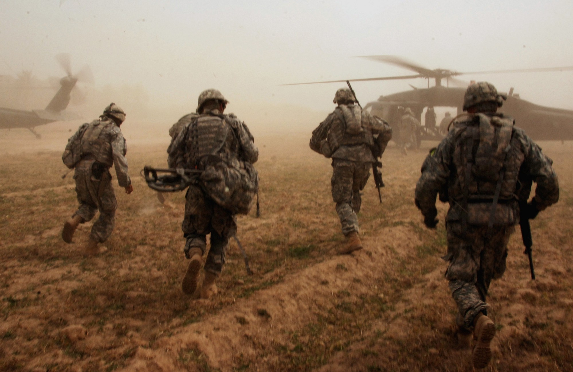 """Image ID: Four US troops run to a helicopter. SEO Title: President Joe Biden ends the War in Iraq—or does he? Subtitle: Since 2003, US presidents have declared an end to """"combat operations"""" in Iraq three times. Will this one stick? keywords: foreign policy, Iraq War, Joe Biden, insurgency, forever war, military"""