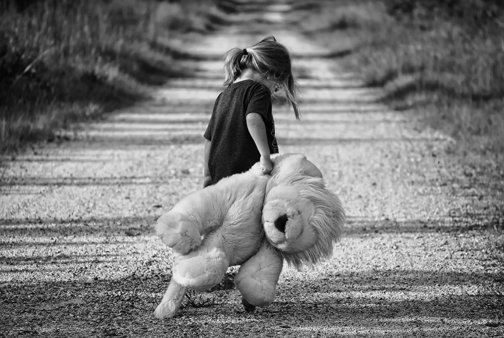 Black and white photograph of lonely girl, dragging teddy bear behind, walking down road alone.