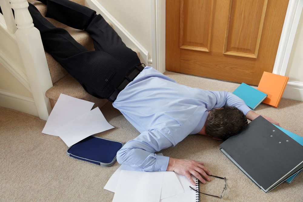 Businessman lying on floor at home surrounded by papers