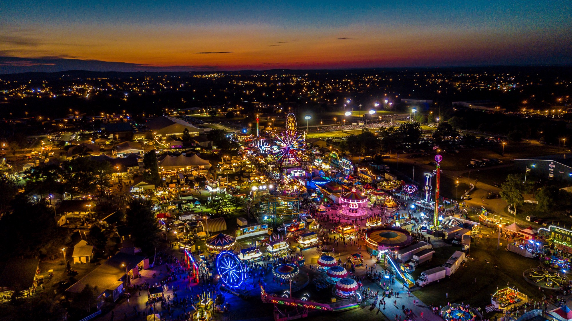Night-time carnival lit up in colorful lights with the sun setting.
