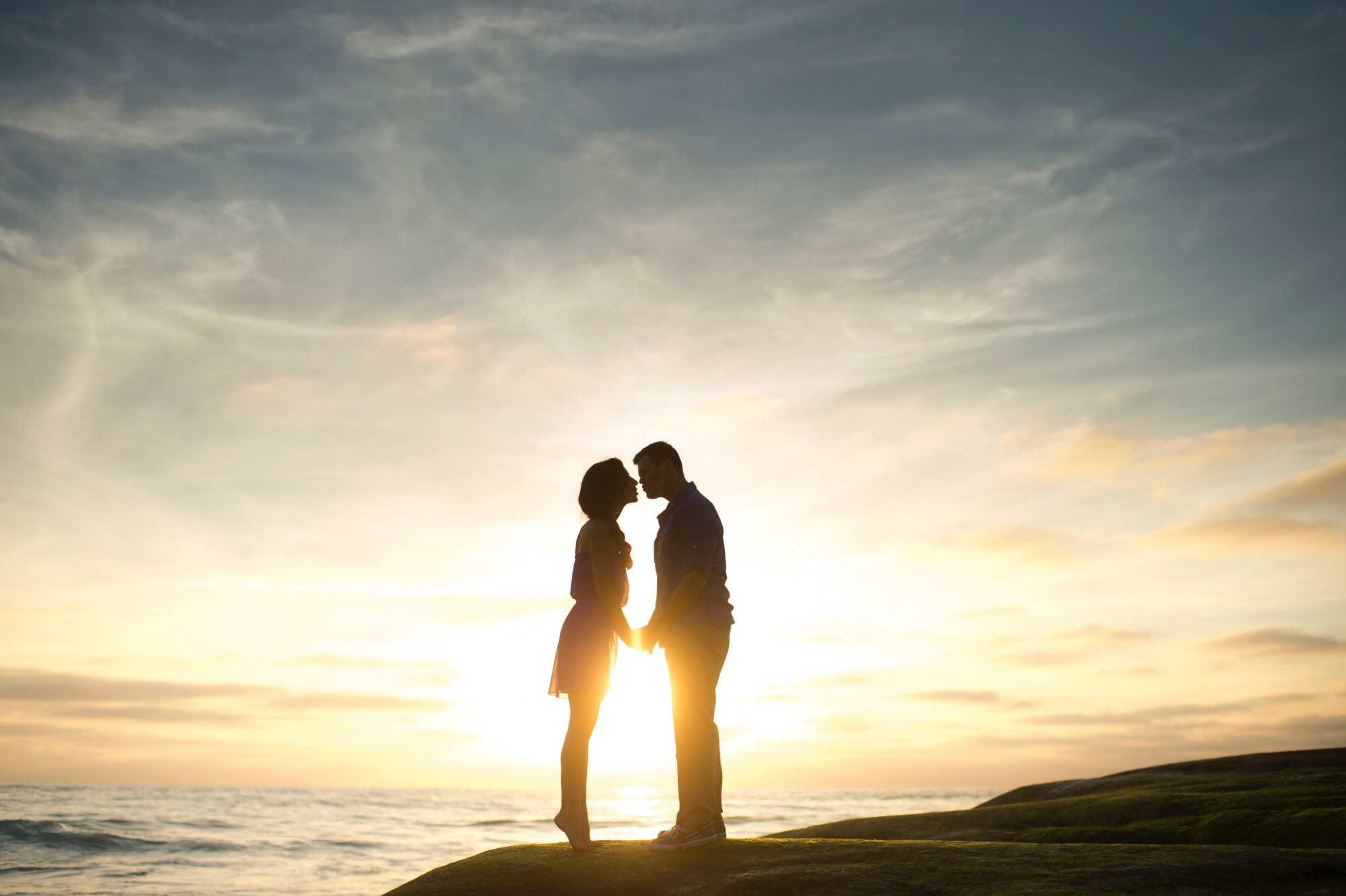A couple overlooking the ocean at sunset, about to kiss.