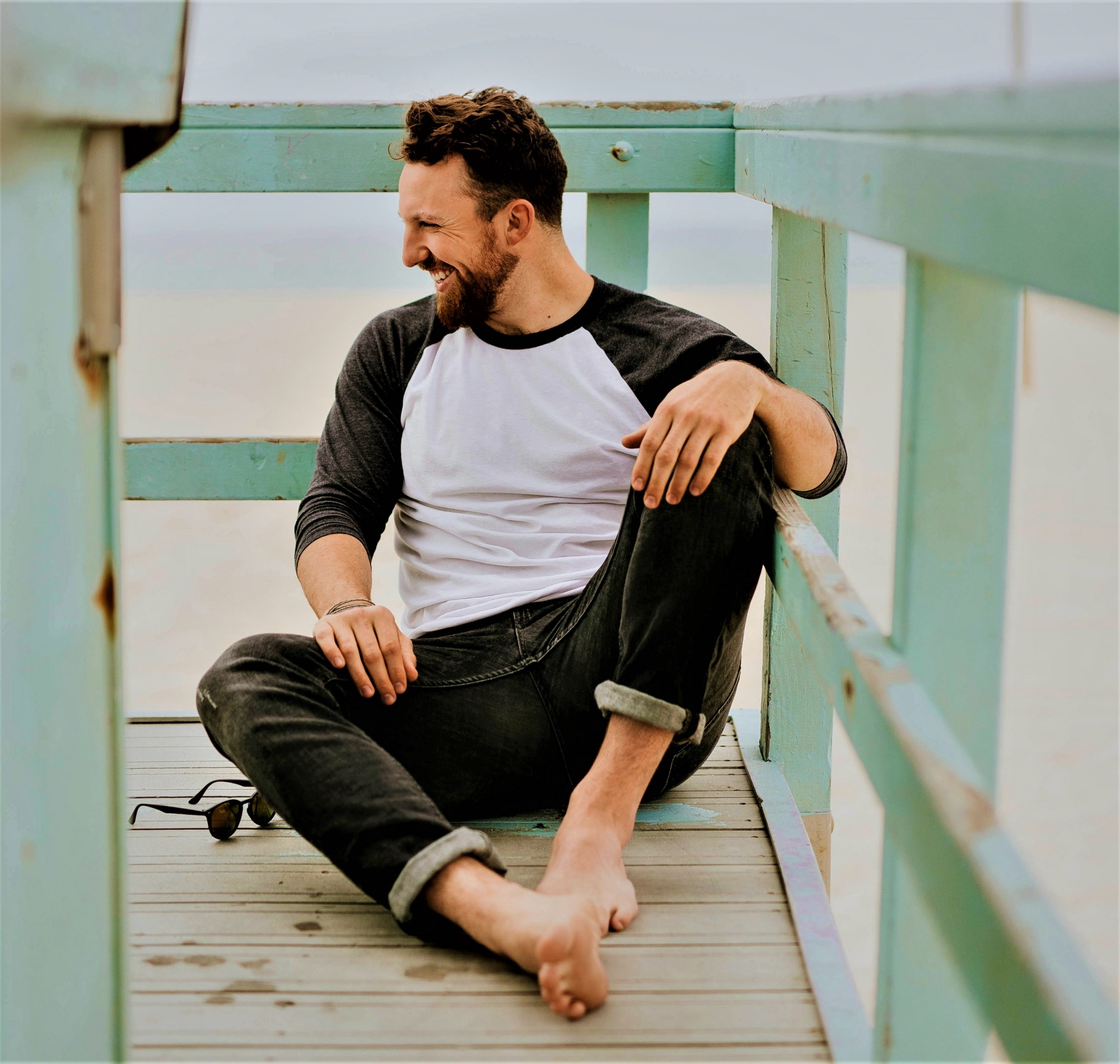 profile of smiling man with beard wearing white and black top and jeans sitting on wooden deck