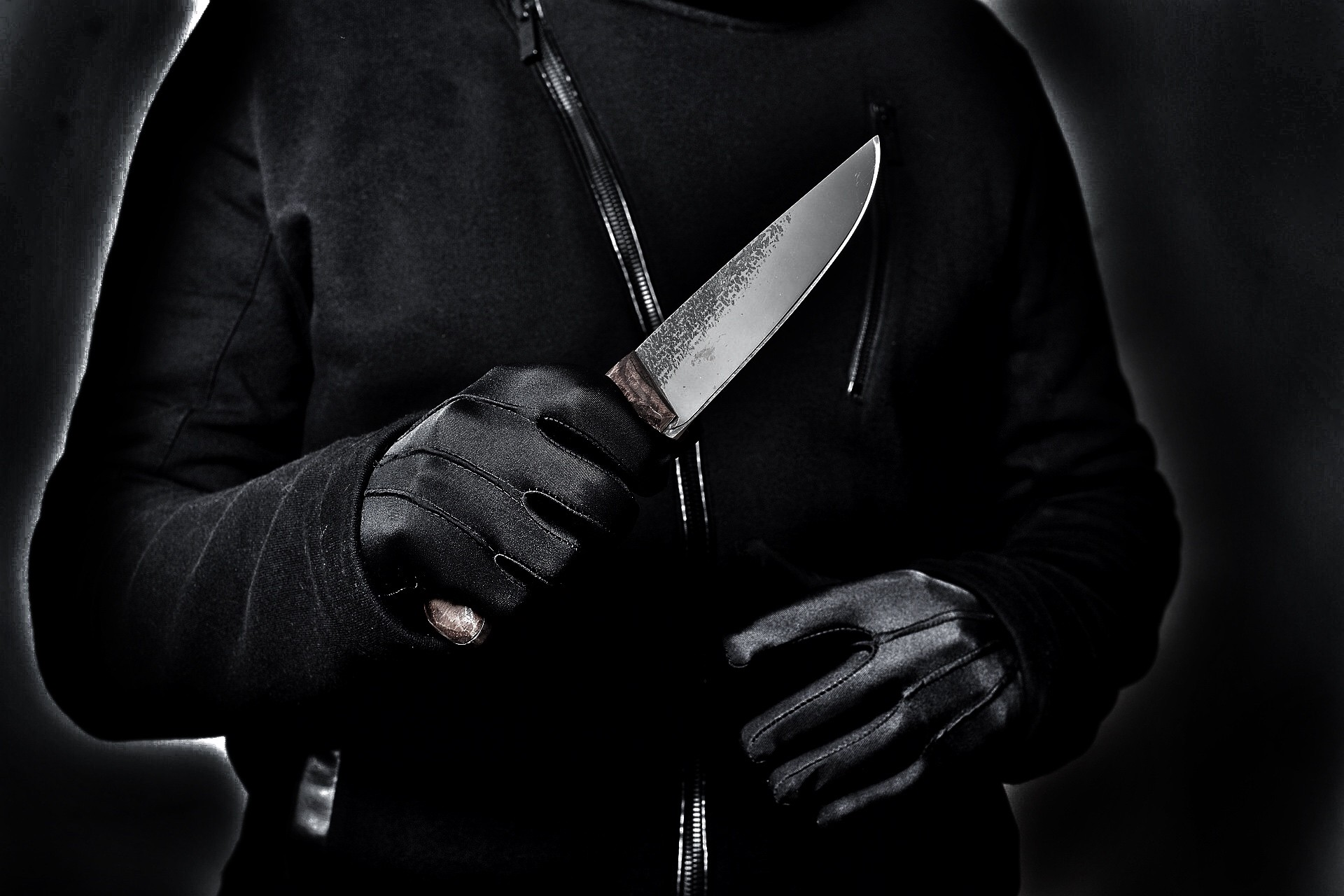 Photo of a person in black with a sharp knife.