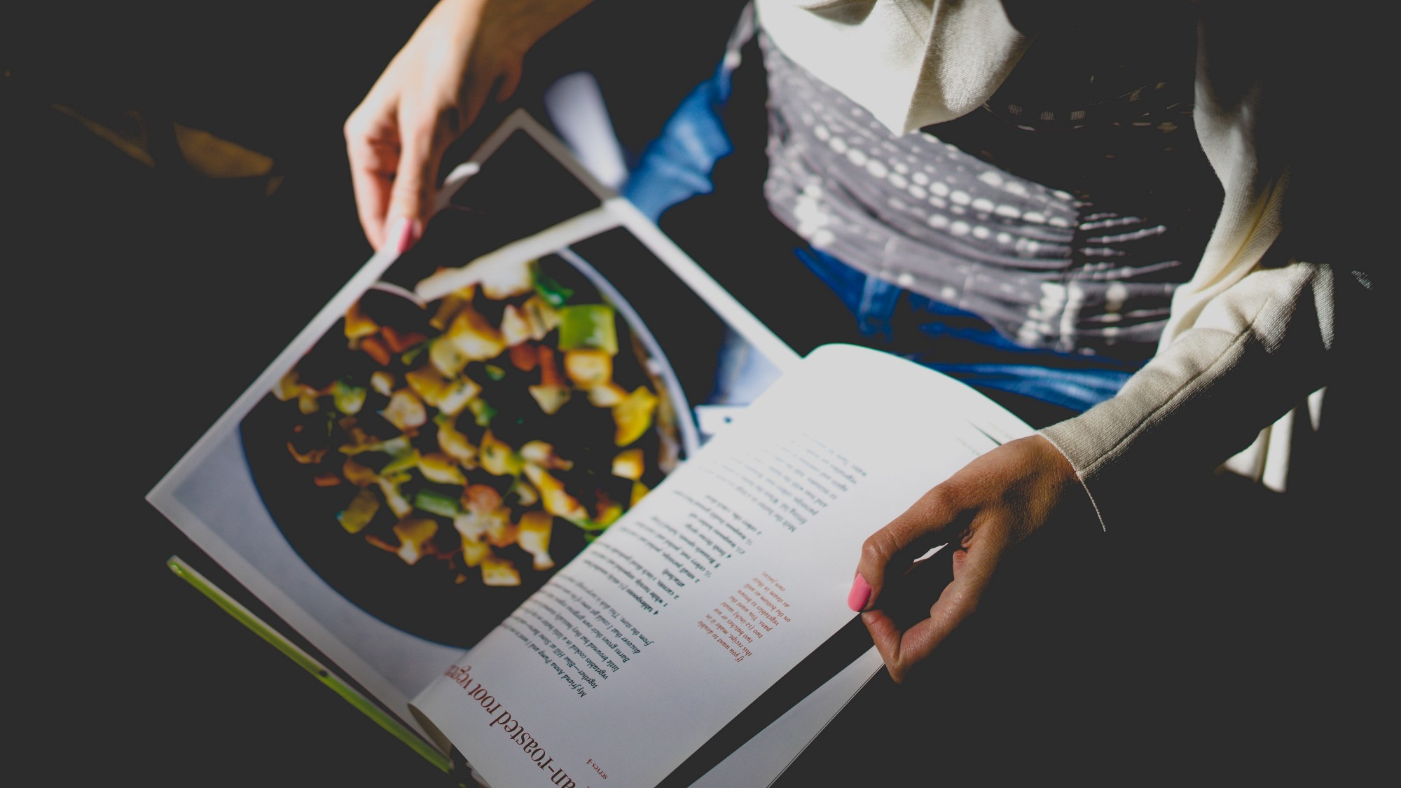 A person's hands holding open a cookbook.