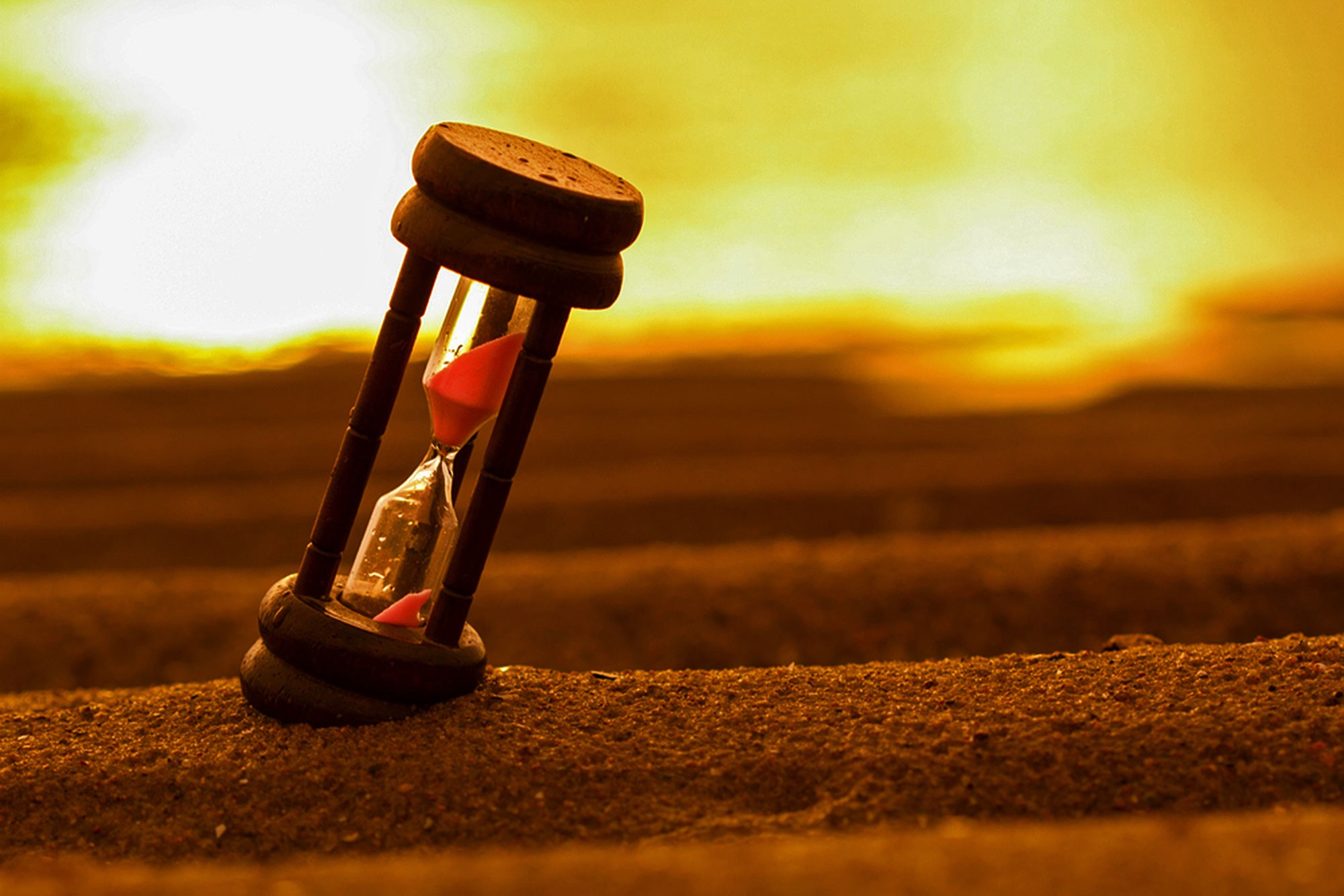Image of a hourglass sand timer sitting on sand (maybe a beach)