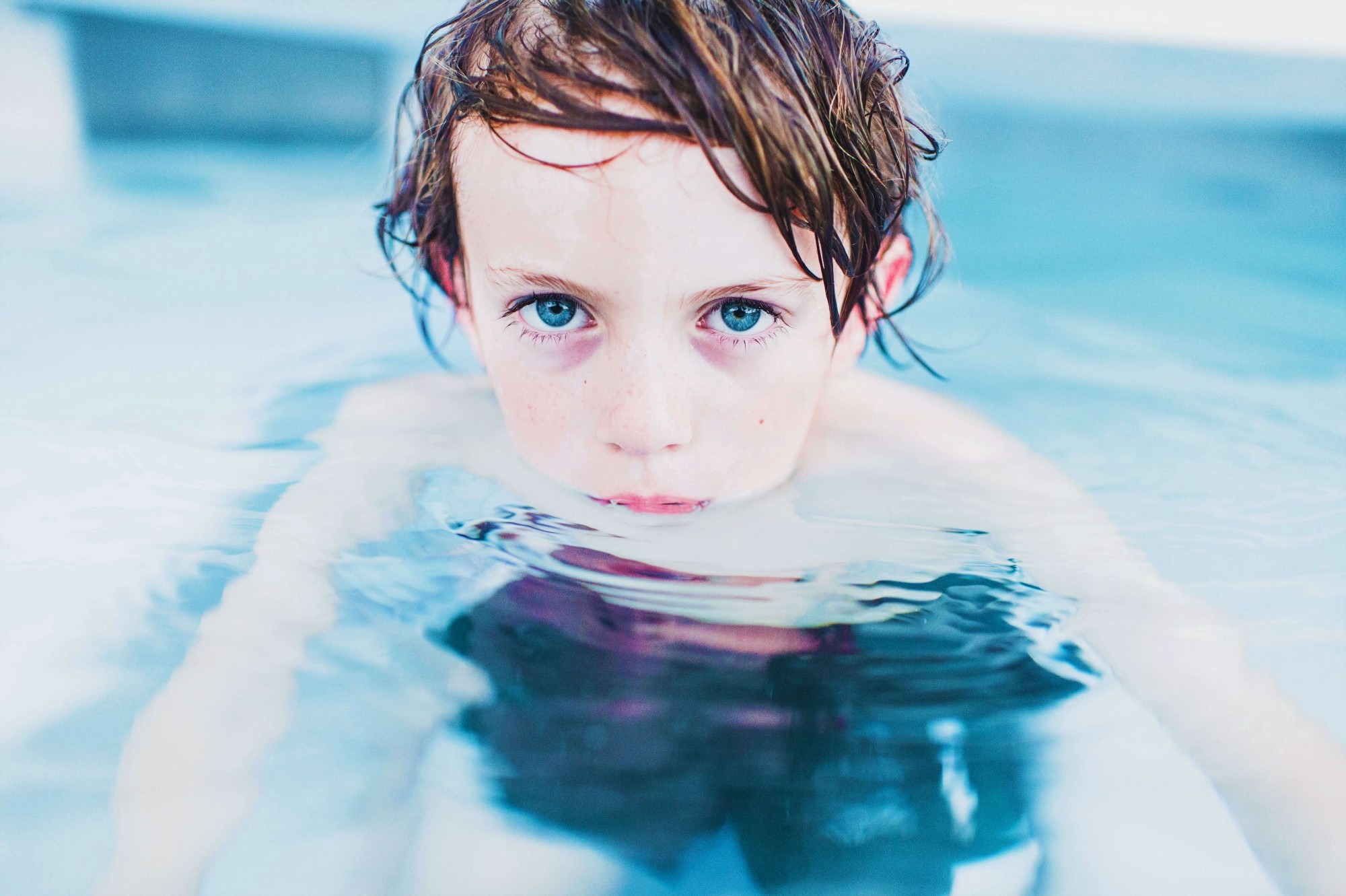 """Young boy swimming in a pool to depict how the baby on the cover of """"Nevermind"""" by Kurt Cobain and Nirvana has grown, and it's coming of age by rising above the water."""