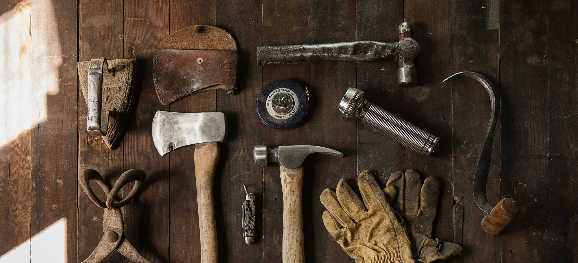 A table displaying a set of tools, like a hammer, an axe and gloves