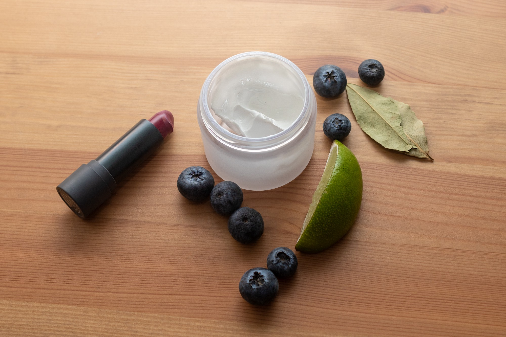 Cream and lipstick sitting on a wood background surrounded by fruit and leaves.