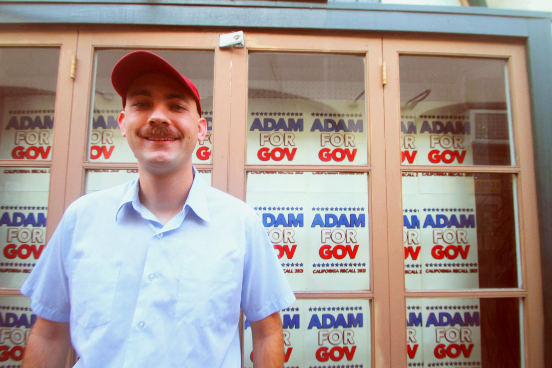 A man with a red cap and blue dress shirt stands in front of a window that has signs saying Adam for Gov