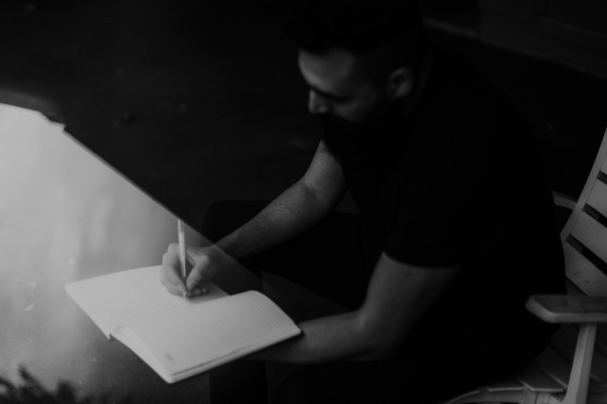 Black and white photo of a man writing in a notebook. The image is dark and faded to create a dramatic effect.