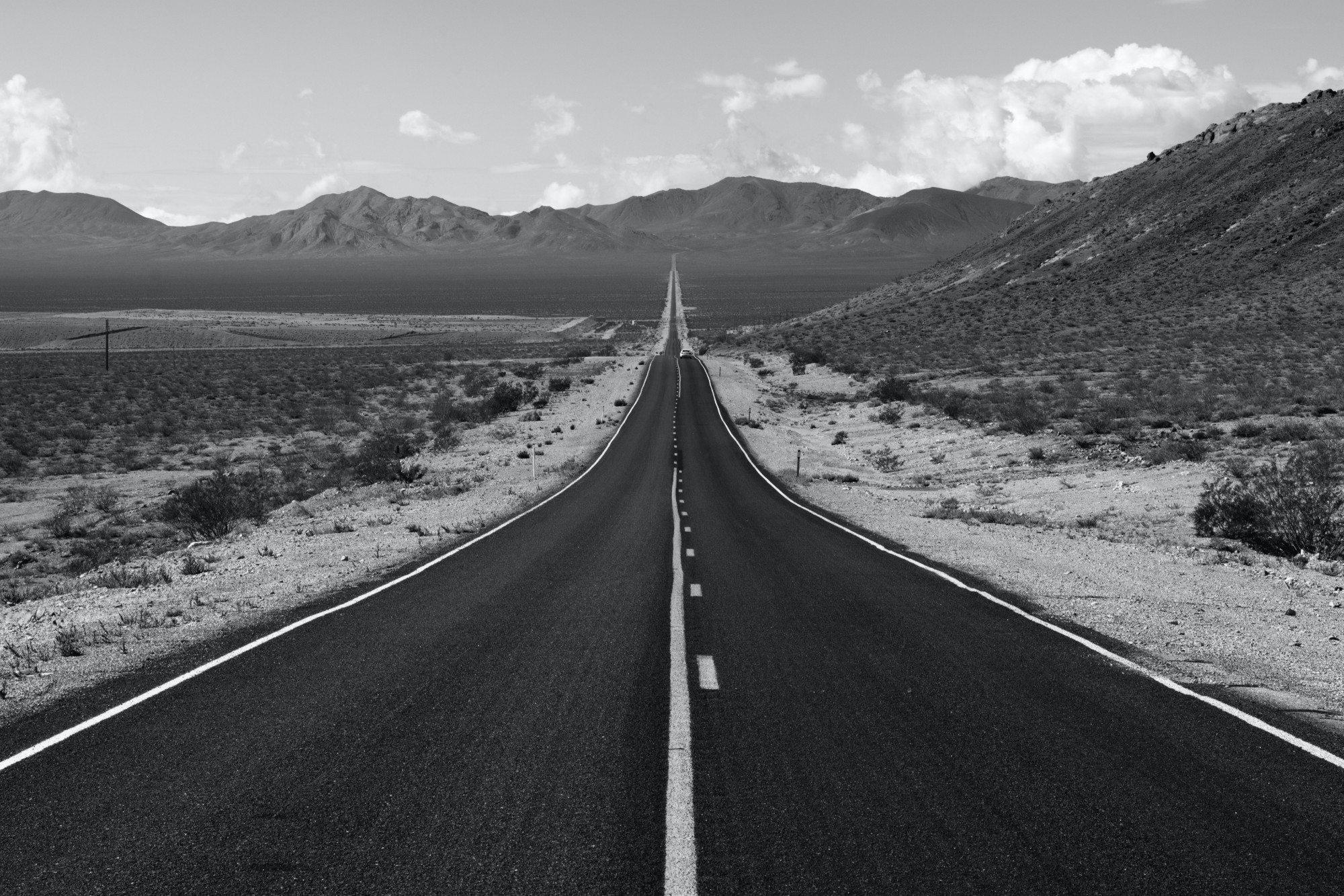 black and white photo of a highway road leading to the horizon