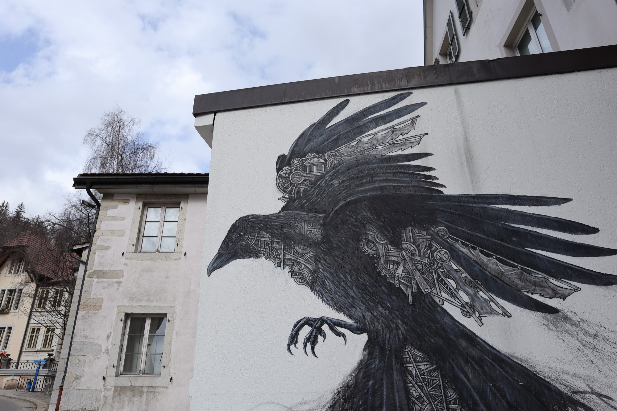 A mural showing a raven with a clockwork in his feathers on a white wall.
