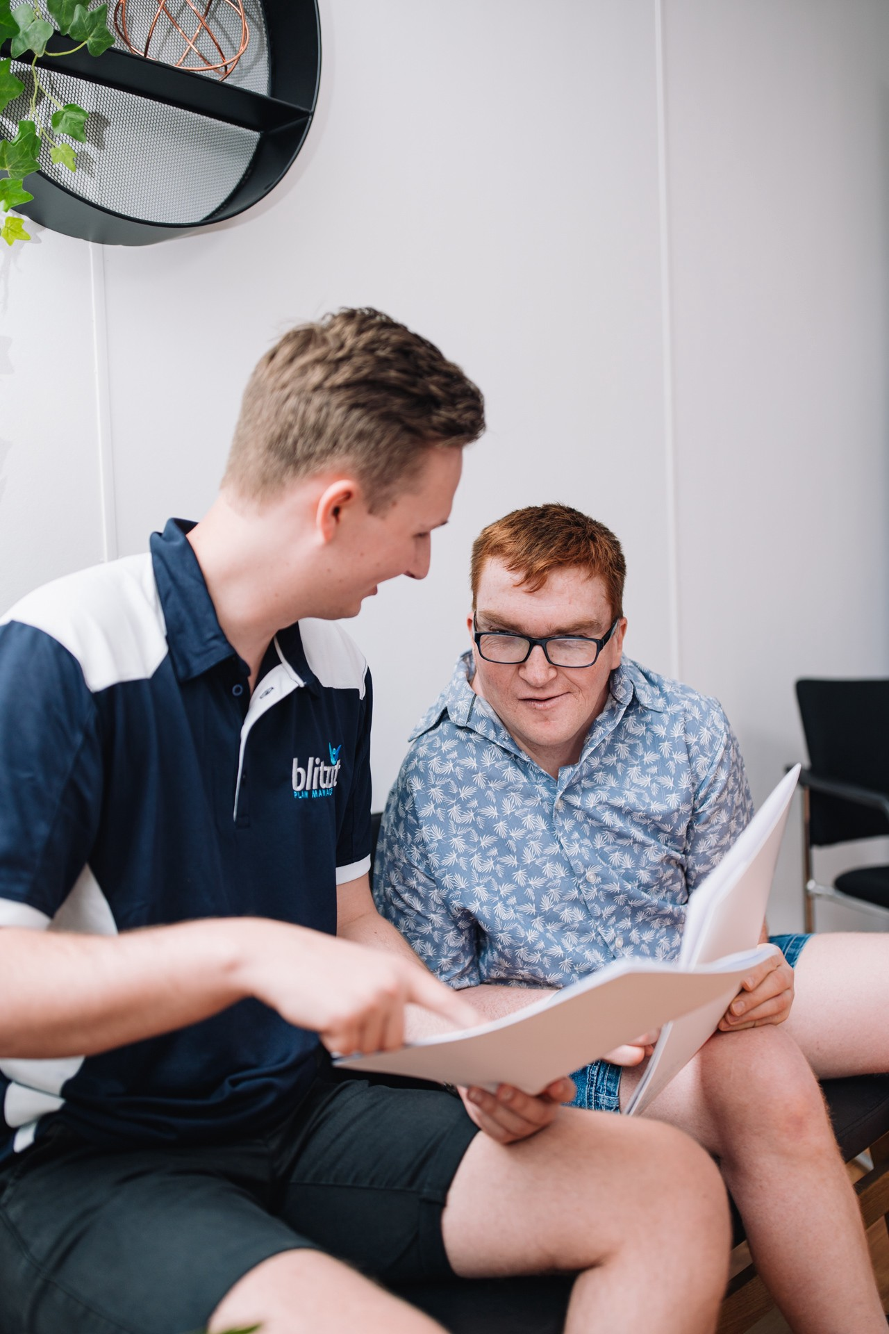 Ned (young male) from the Blitzit Team is showing a participant papers on how Blitzit can help with their NDIS plan. Ned is at the front in a Blue & White Blitzit shirt and the Male Participant who wears glasses and has red hair, wearing a light blue patterned shirt, is looking at the papers. They sit on a plain background.