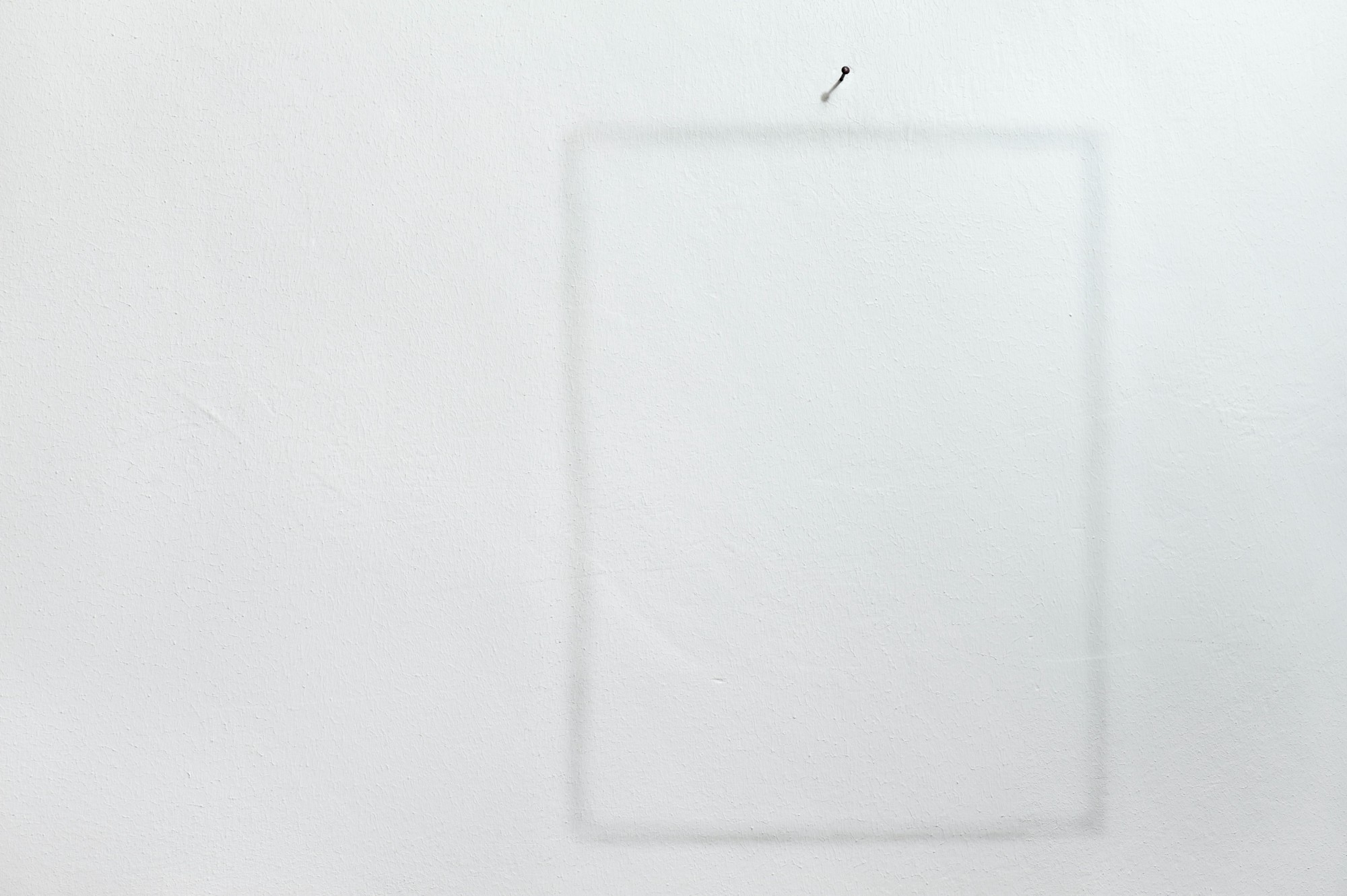 A white wall with an outline of a picture frame, with a nail above it.
