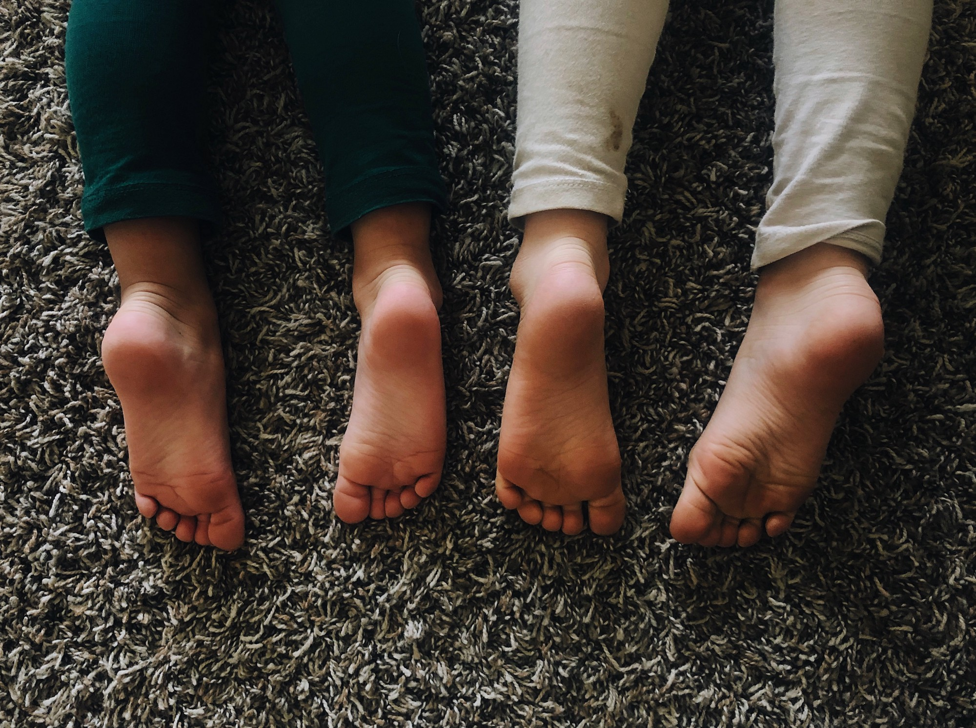 My daughter's bare feet on our living room floor.