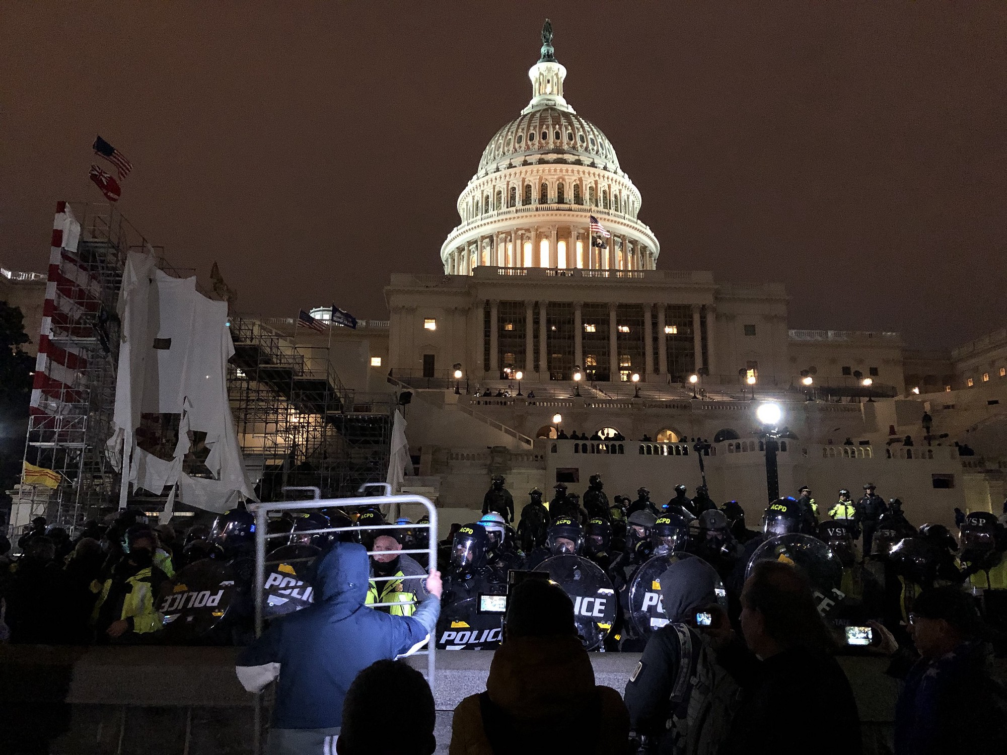 Image ID: A line of Capitol police officers with round riot shields stands in front of the Capitol building at night. On the other side there is a crowd taking pictures with their cell phones. A man in front holds up a piece of metal temporary police fence. SEO Title: Democrats are presenting Capitol cops as 'heroes' as a backdoor means of rehabilitating police. Keywords: Joe Biden, Capitol riots, insurrection, January 6, Democrats, Donald Trump