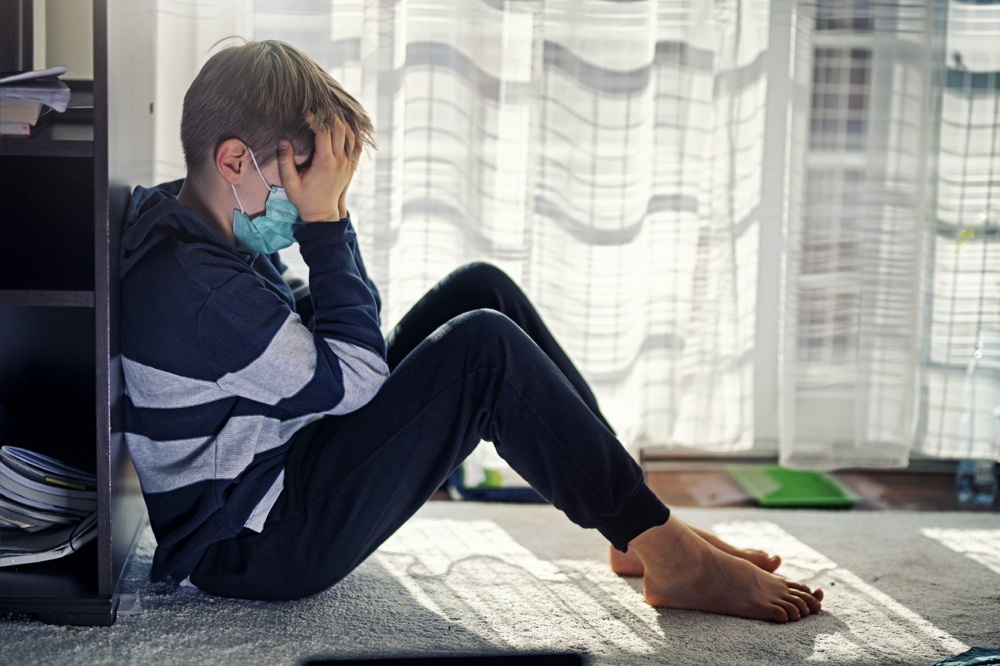 Child sits on floor near a window with head in hands. Photo by Imgorthand/Getty Images