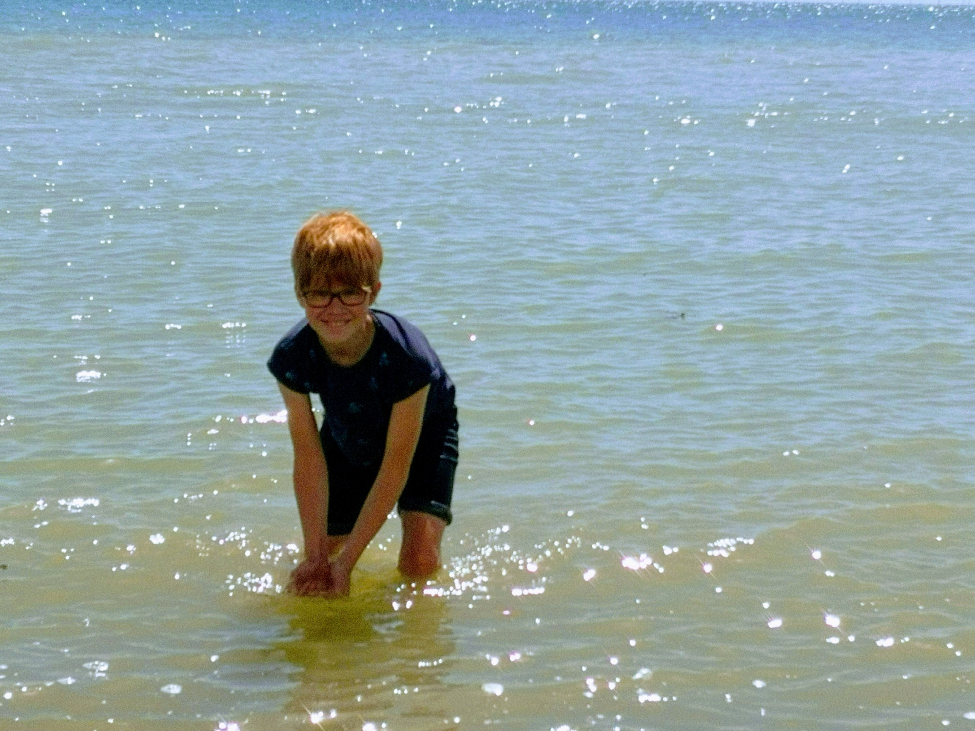 Smiling child in sparkling sea ready to splash