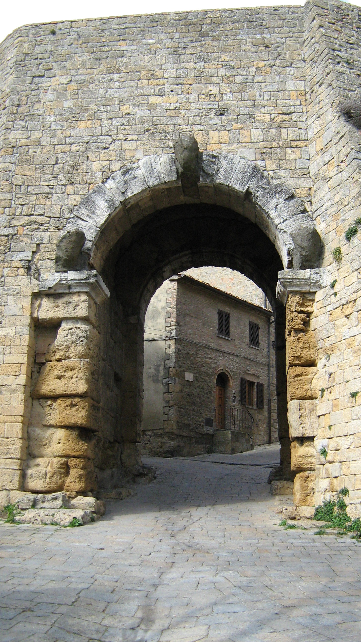 Colour photograph of a medieval arch and house in Volterra