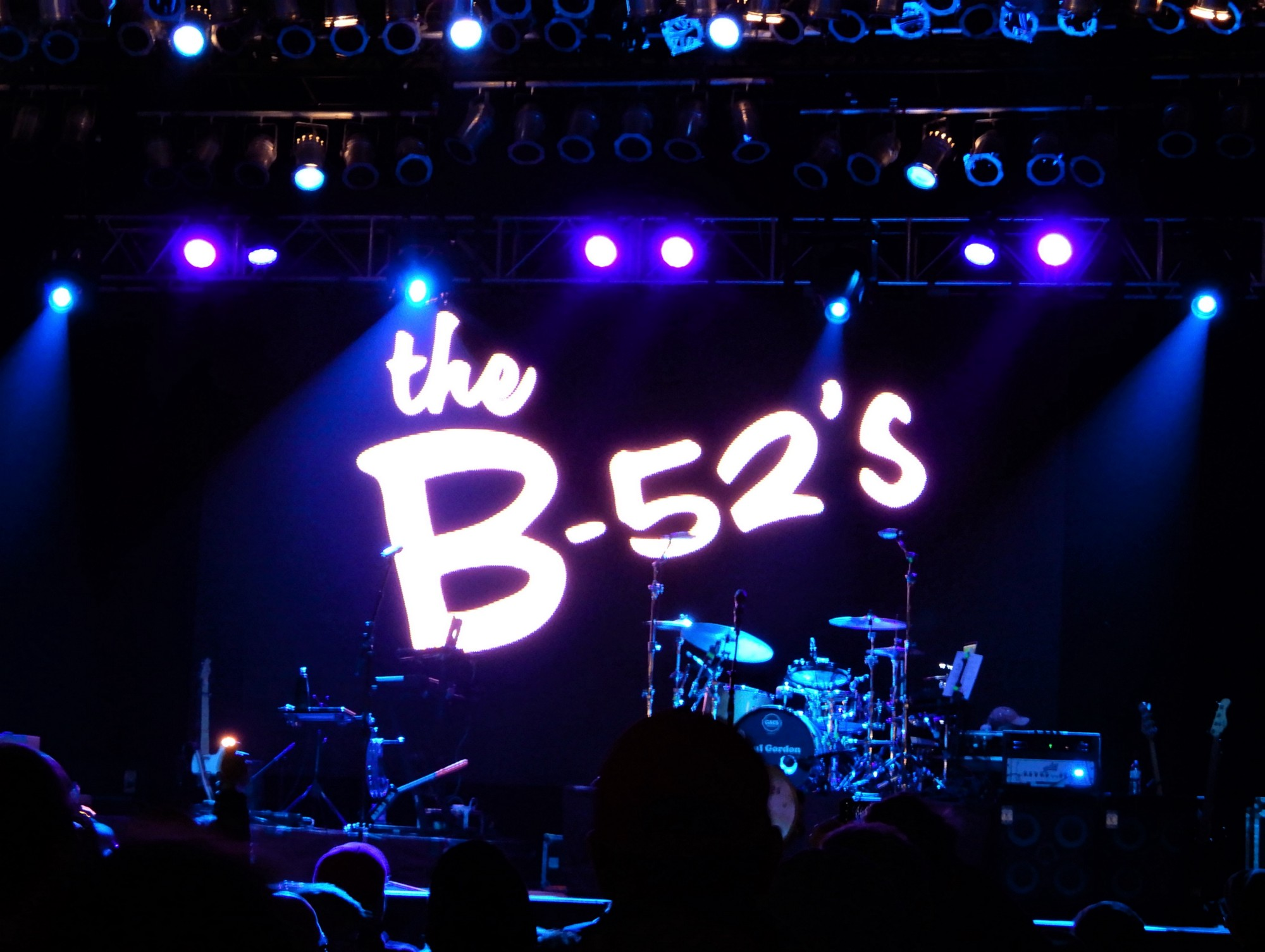Stage with lit with spotlights and projection of B-52's logo behind drum kit.