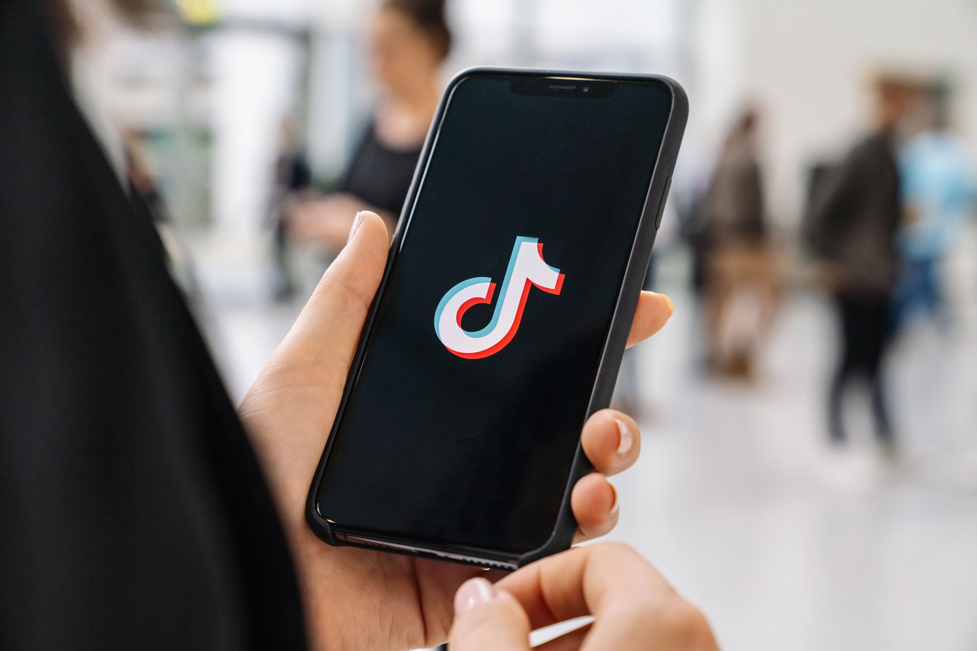 A person holding up a phone with a splash screen with the TikTok logo