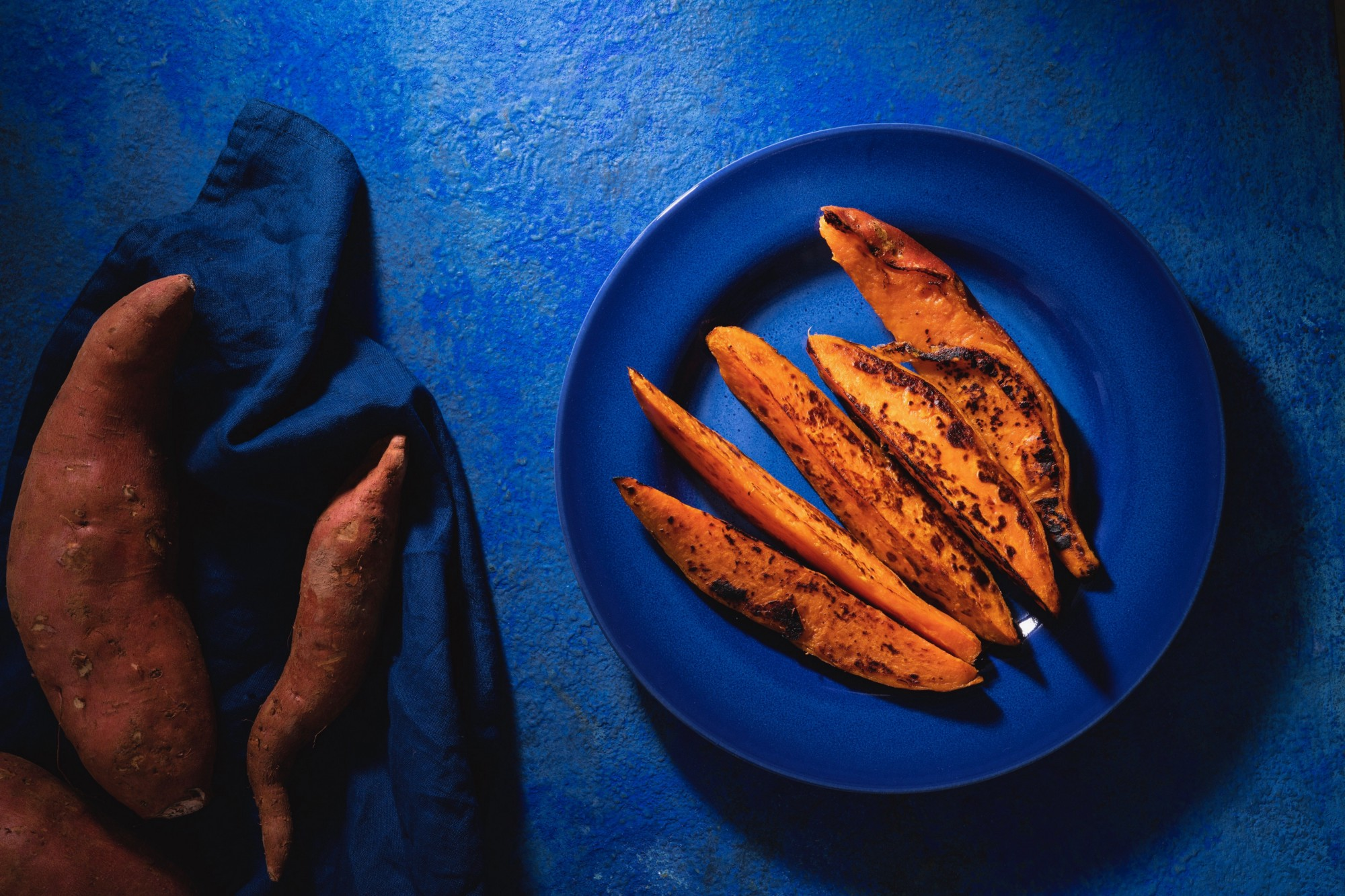 Cooked sweet potatoes on a blue plate