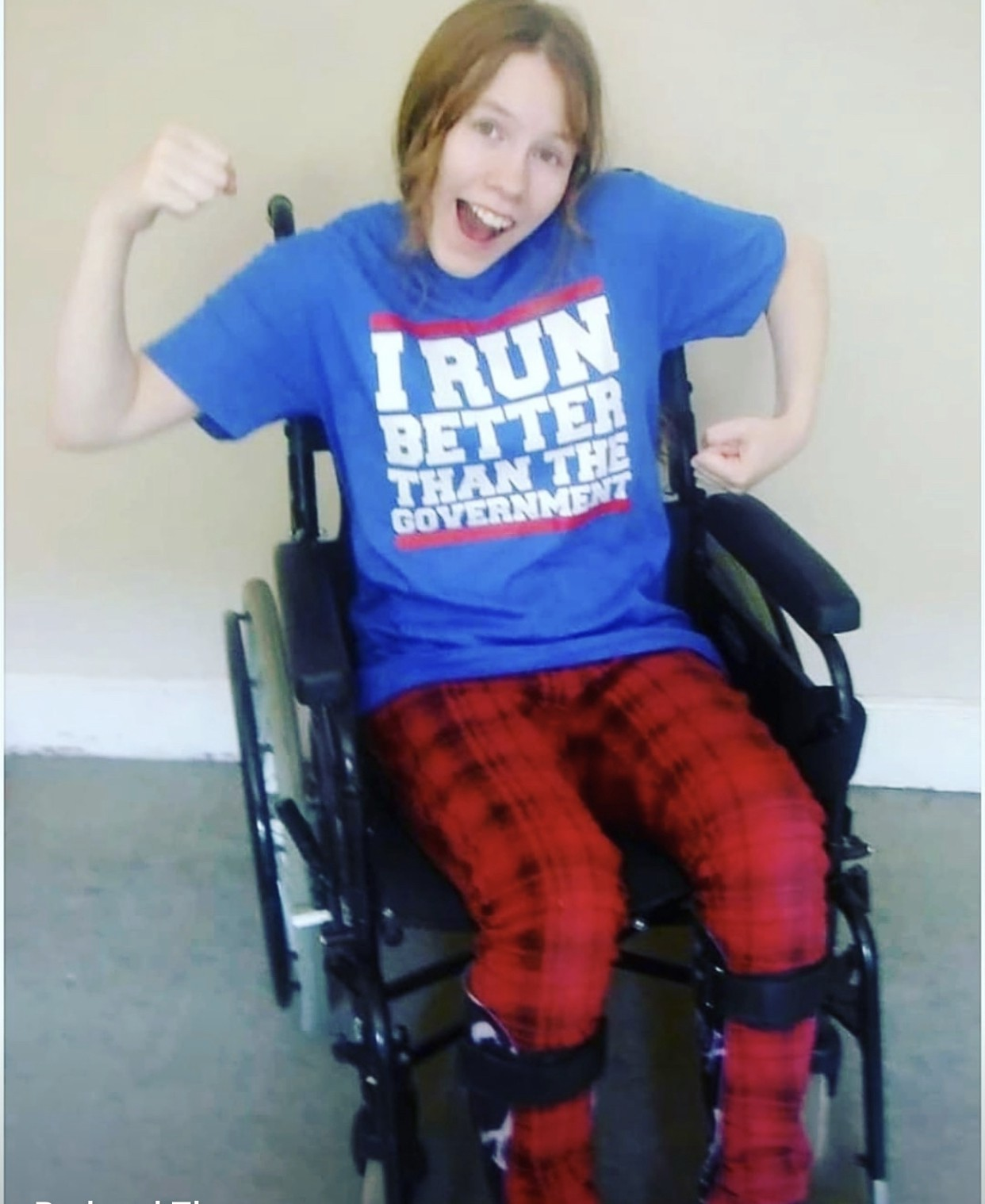 "A girl in a wheelchair wearing a shirt that says, ""I run better than the government"""