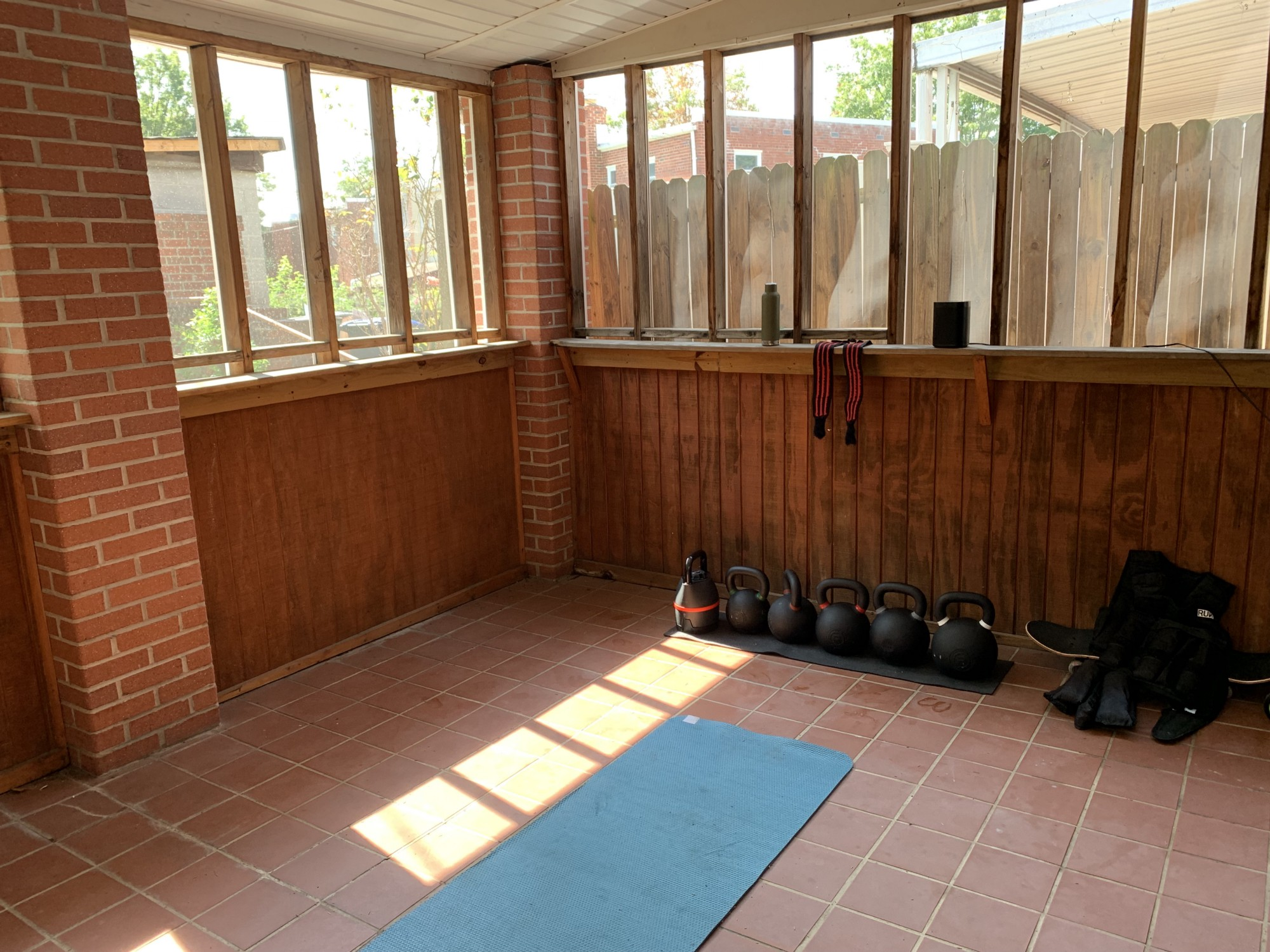 Picture of a three season porch with a yoga mat on the floor, a row of kettlebells next to it and other various fitness equipment around.