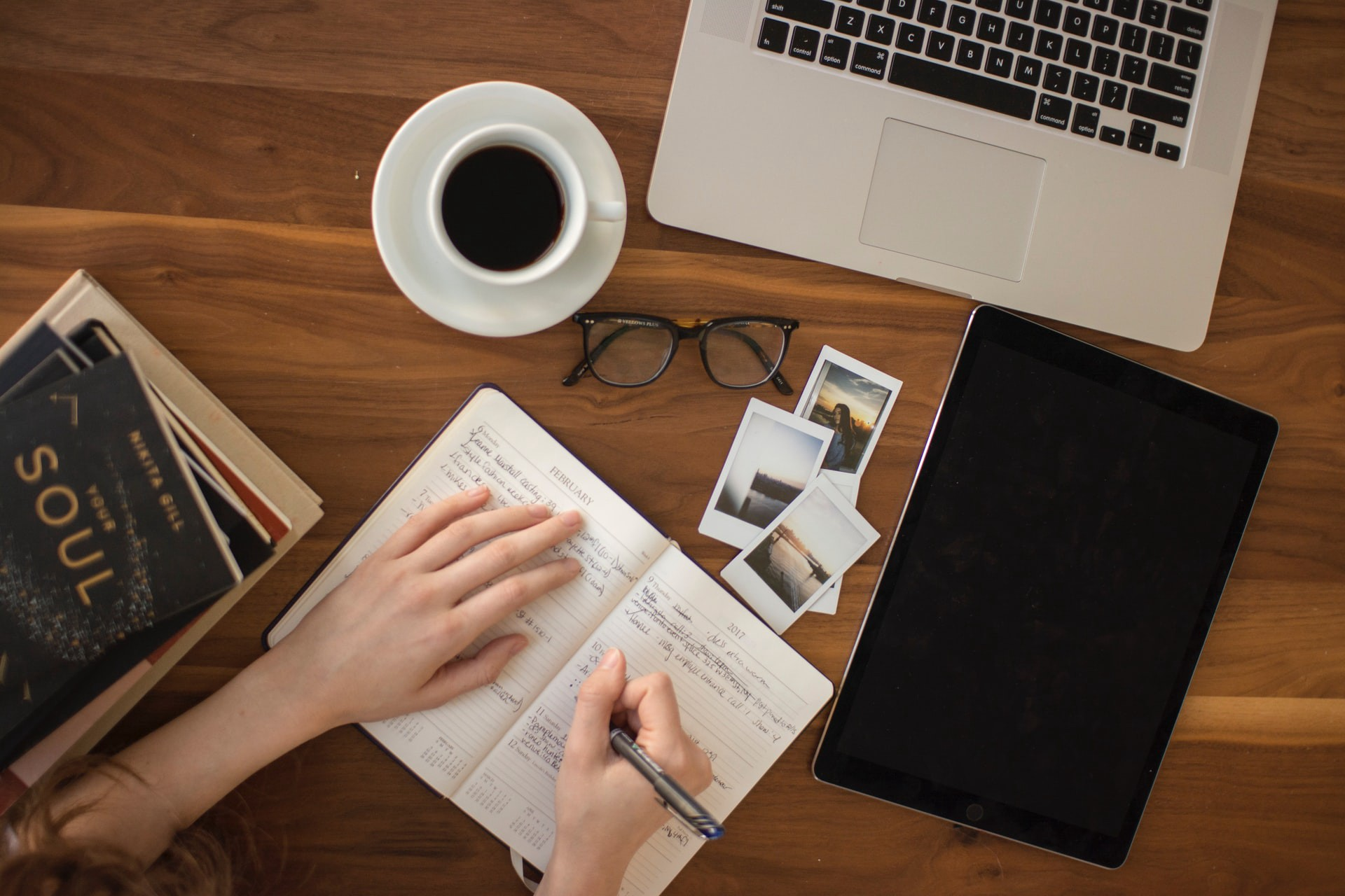 A person writing in a notebook. A book, another black notebook, coffee cup, spectacle and macbook keyboard is visible.
