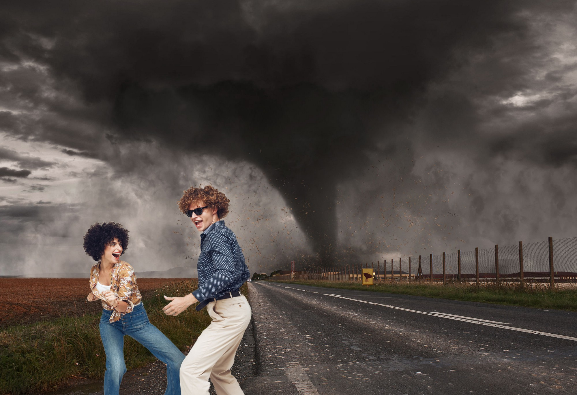 Couple dances in front of a tornado in an exagerrated example of hope.