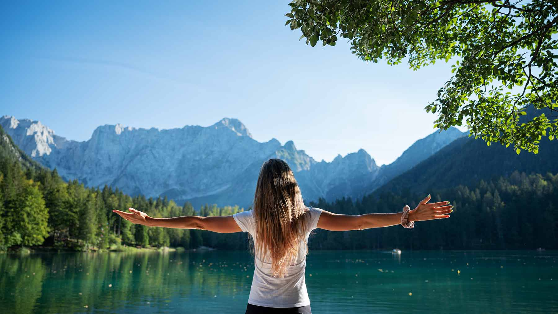 A woman stands with her arms wide open. She's looking at a calming landscape of water and greenery.