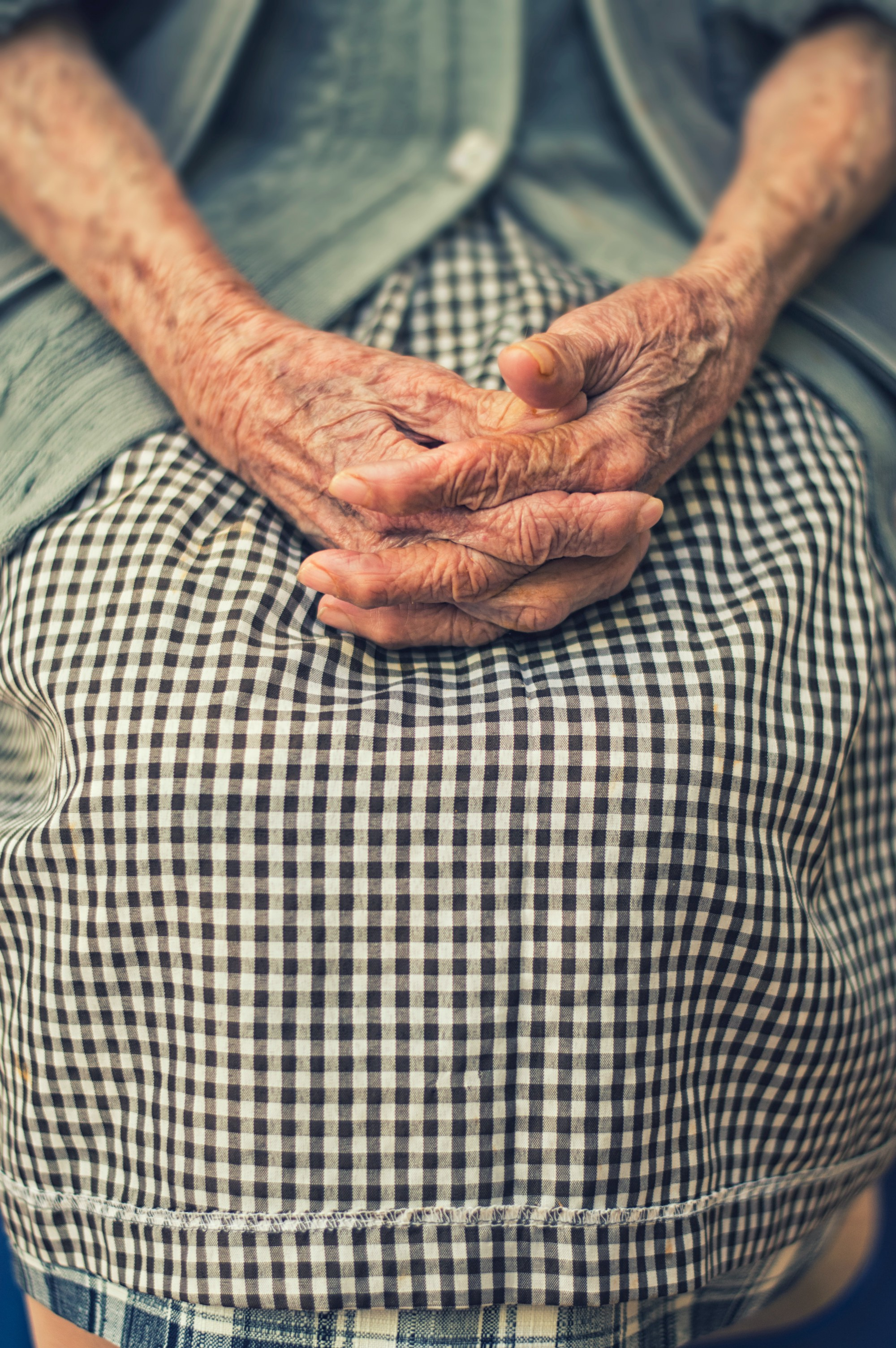 A close up picture of an elderly woman's hands as they rest in her lap