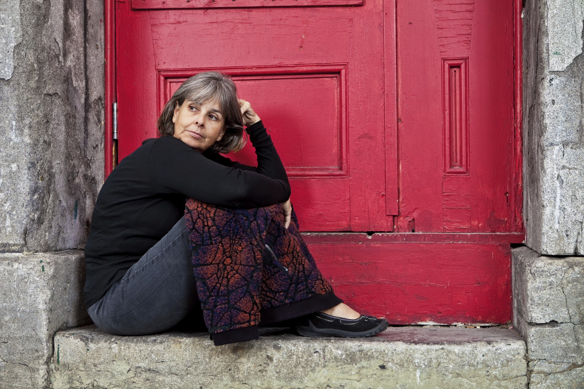 A respectable looking middle-aged woman sits in a doorway with a blanket over her knees