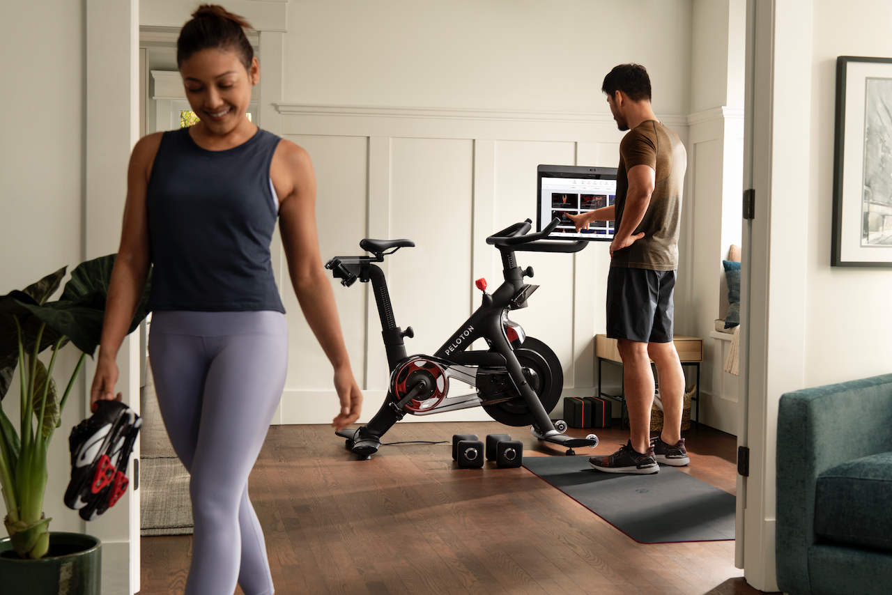 Two people working out at home using a Peloton cycle