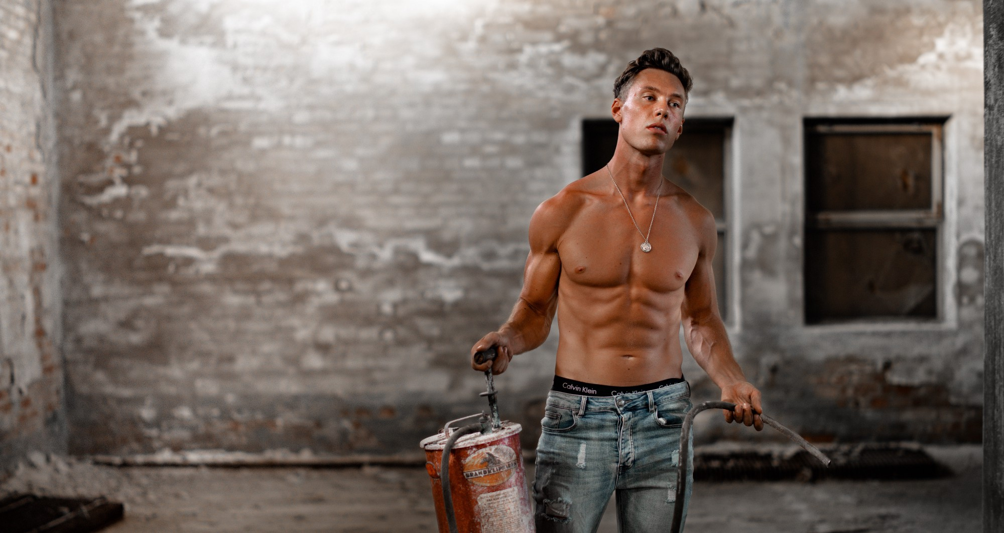 Shirtless tanned white man in jeans carrying a fire extinguisher