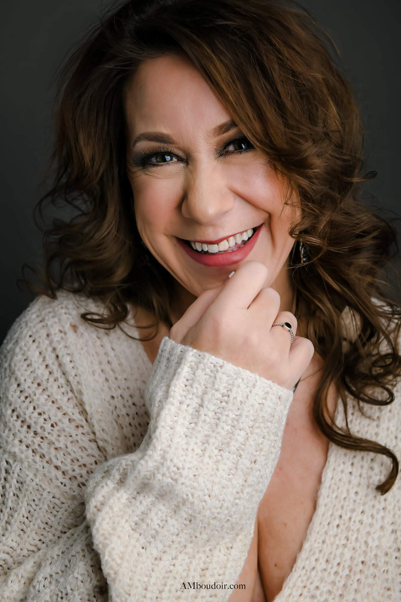 White woman smiling with beige sweater hand at her mouth brown hair curly mauve lipstick and dark eye shadow with brown eye