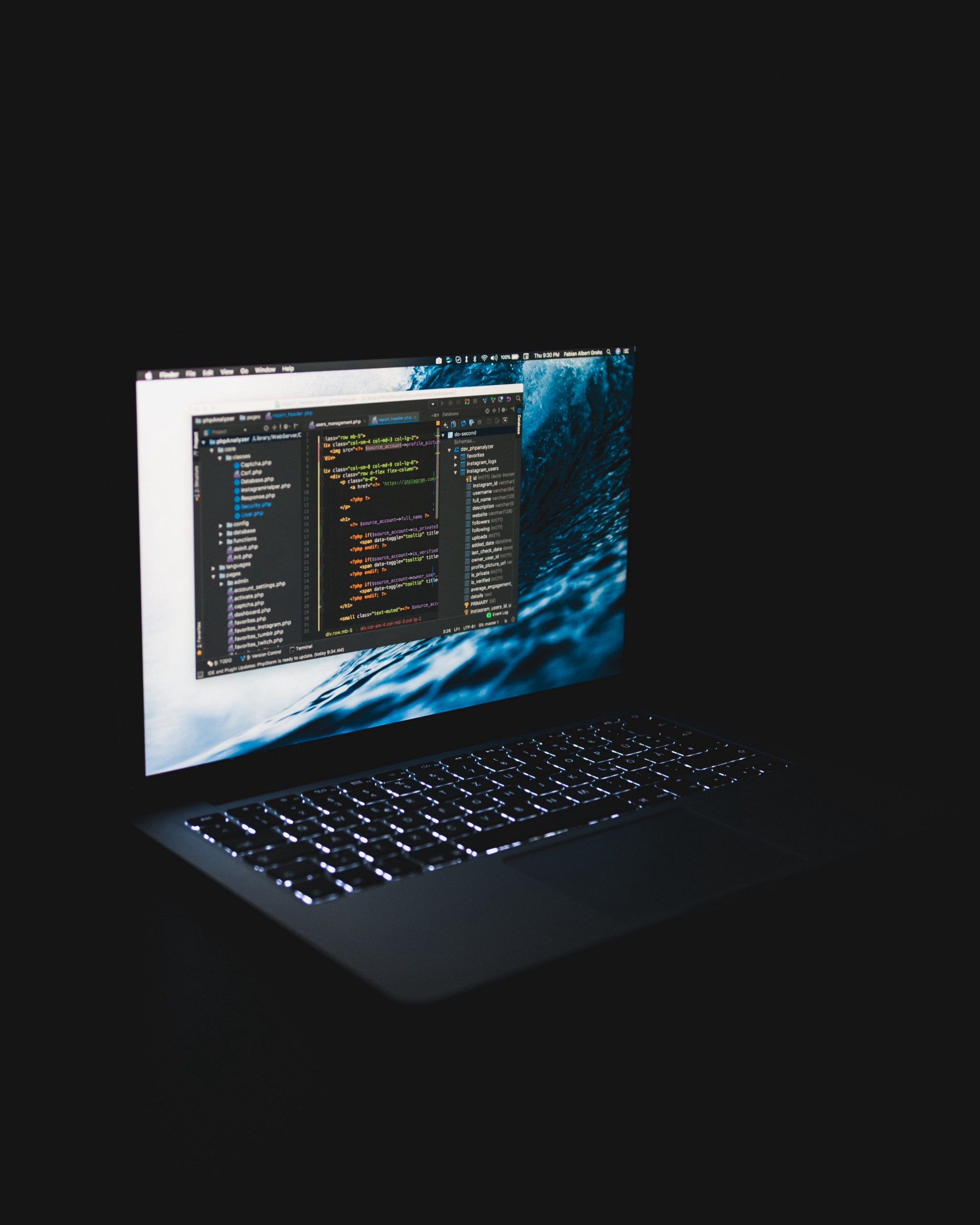 An apple laptop in a dark room with vscode running
