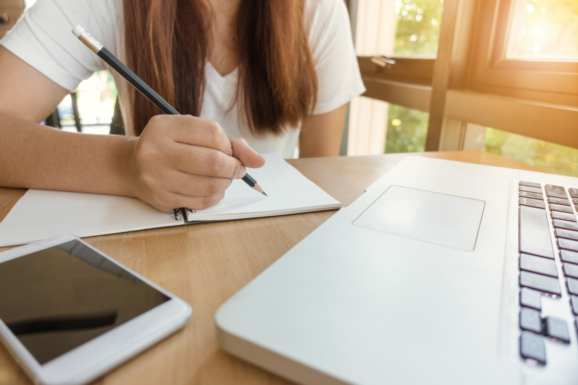 Woman about to write on a paper notebook