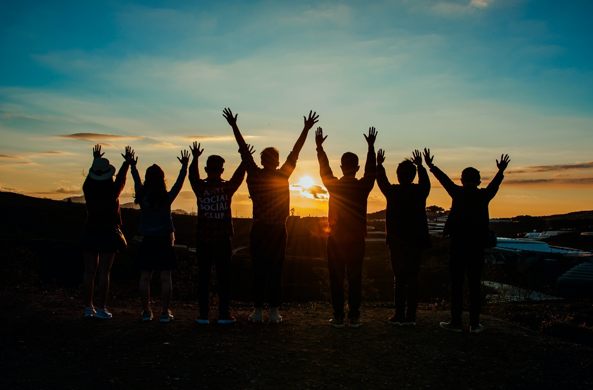 A group of people in front of a sunset cheering