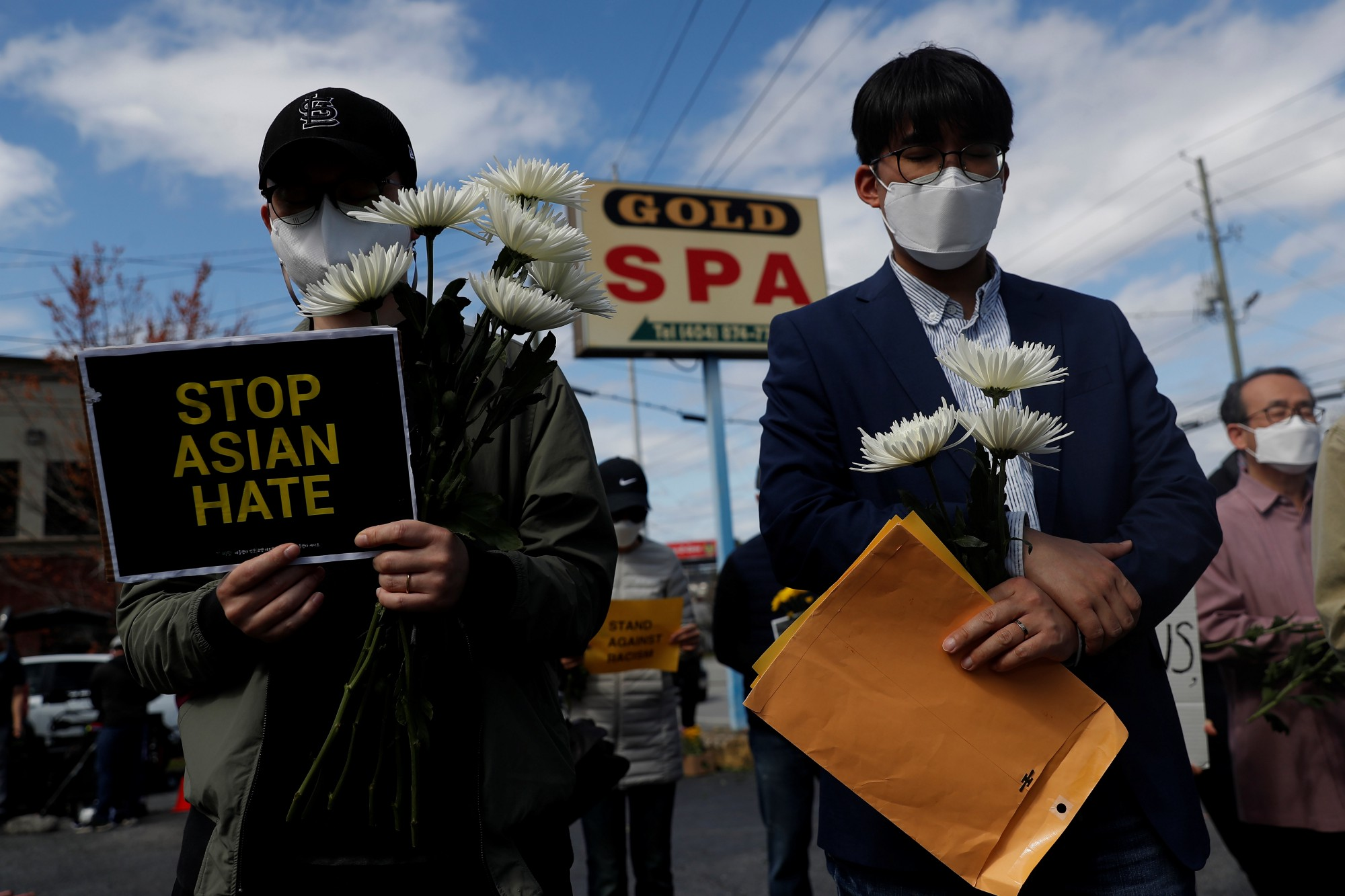 Men hold flowers during a vigil at a makeshift memorial outside the Gold Spa following the deadly shootings in Atlanta, Georgia, March 21, 2021. Photo by Shannon Stapleton/Reuters