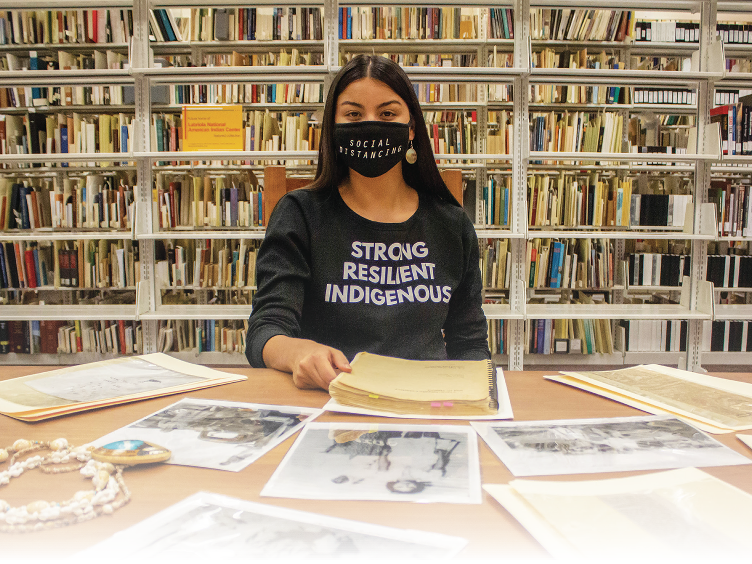 """Lourdes is sitting at a table sprawled with documents at ASU's Labriola Center. In the background are rows of books. Lourdes is wearing a black """"Strong Resilient Indigenous"""" shirt and a black face mask."""