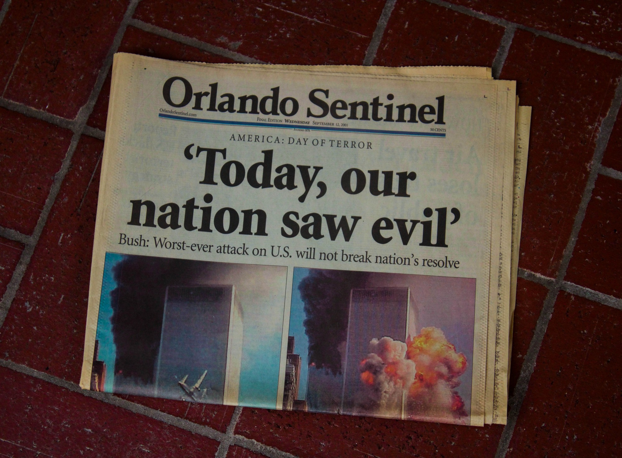 Pictured is the cover of the Orlando Sentinel newspaper coverage on Sept 12, 2001. The headline states: 'Today, our nation saw evil' and the story photo shows both of the Twin Towers surrounded by smoke and explosions.