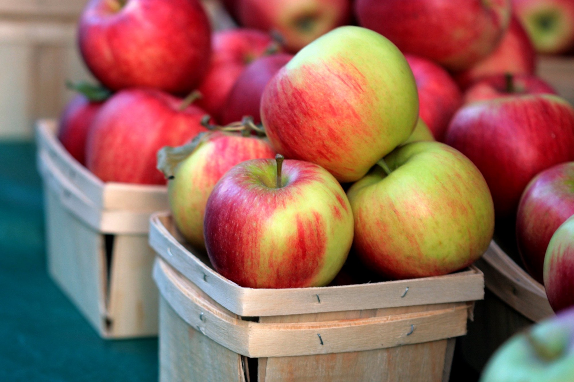 Red apples in small wooden baskets for sale at a farmers market.