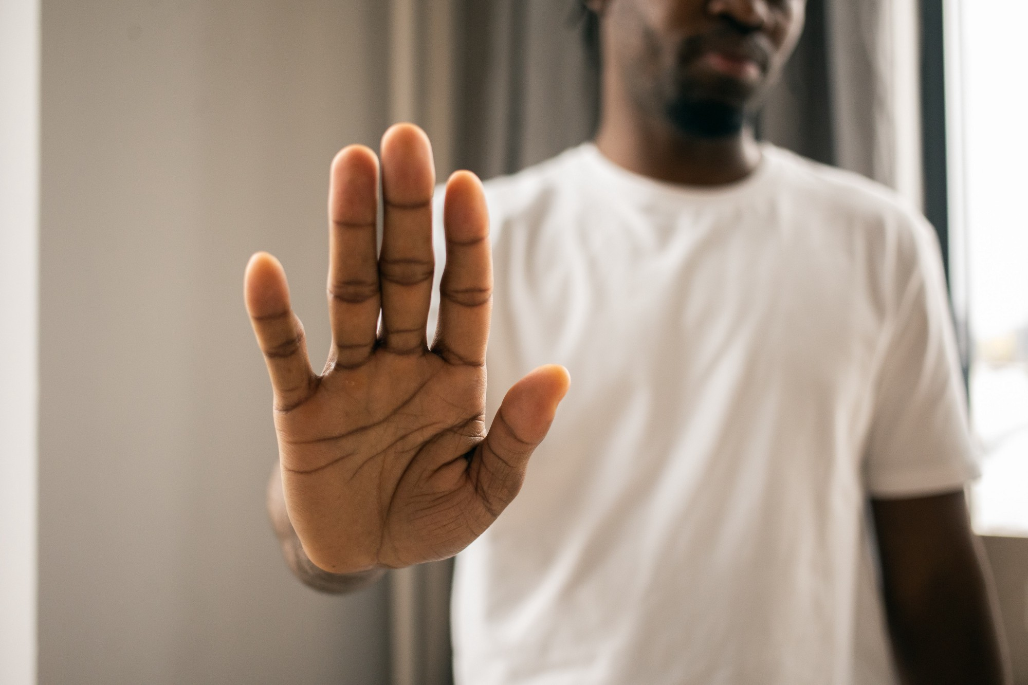 A man holding his hand out in front to signal, stop!