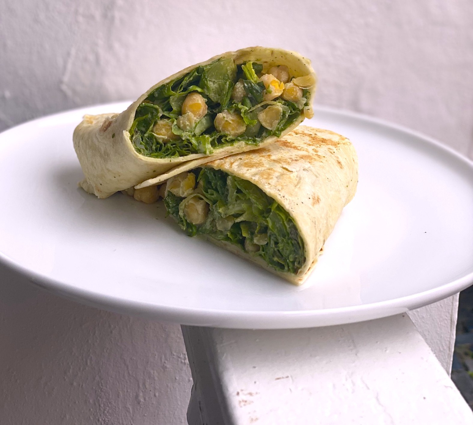 Chickpeas and lettuce shimmering with a creamy caesar dressing, stuffed into a large tortilla folded wrap-style.