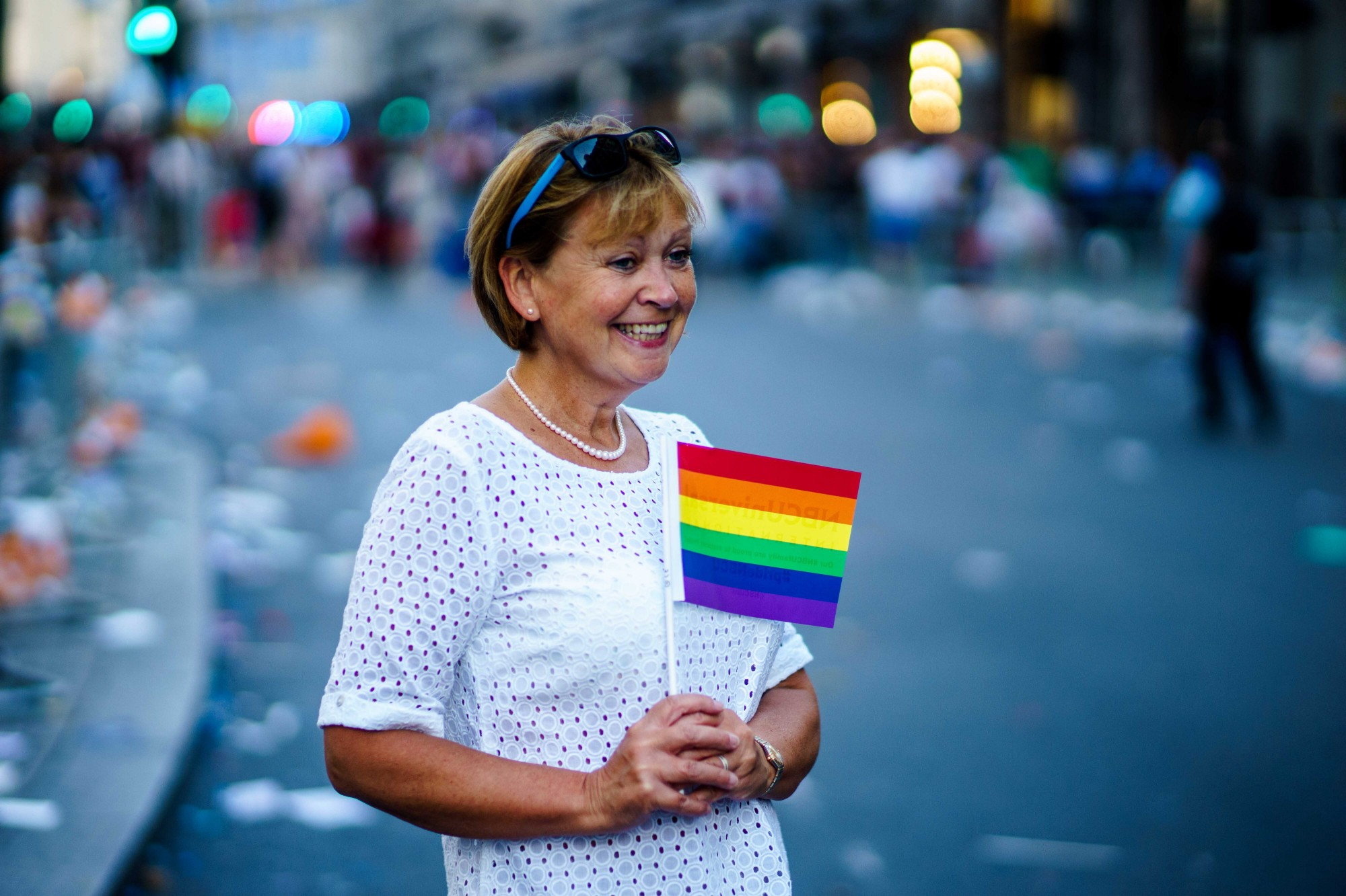 A white woman who looks to be young grandmother age, stands on a parade route, holding a small rainbow flag and smiling.