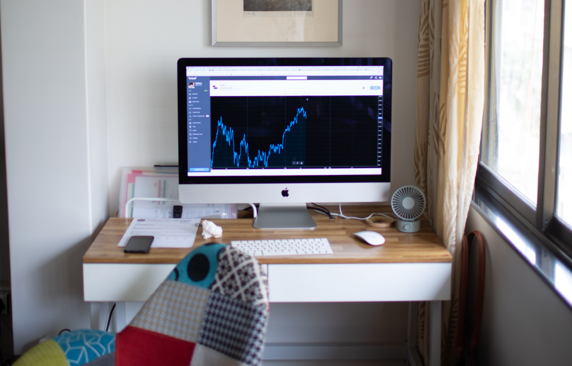 iMac with a stock chart on the screen, sitting on a wooden desk.